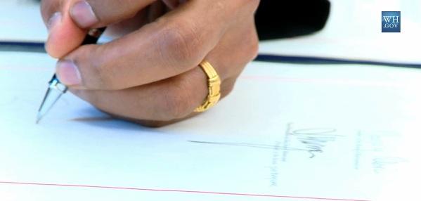 obama signing legislation with his muslim ring - Obama Wedding Ring